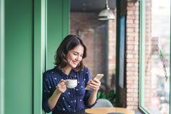 咖啡馆的美丽的逗人喜爱的亚裔年轻女实业家,使用mobi 免版税库存照片