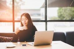 咖啡馆的美丽的逗人喜爱的亚洲女孩在与咖啡微笑和工作区的窗口附近,放松 免版税库存图片