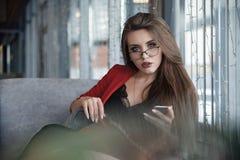 咖啡馆的美丽的逗人喜爱的年轻女实业家,使用手机和饮用的咖啡微笑 库存照片