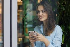 咖啡馆的美丽的逗人喜爱的白种人少妇,使用手机和身分在窗口微笑附近 图库摄影