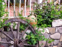 咖啡馆的街道装饰:花、一个古老车轮和老黏土水罐 库存图片