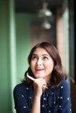 咖啡馆的年轻美丽的妇女在窗口附近,认为和写某事 库存图片