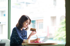 咖啡馆的年轻美丽的妇女在窗口附近,认为和 免版税图库摄影