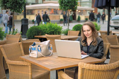 咖啡馆膝上型计算机俏丽的坐的街道妇女 库存图片