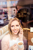 咖啡馆饮用的咖啡的妇女,打电话 免版税库存照片