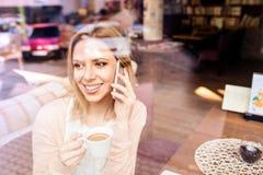 咖啡馆饮用的咖啡的妇女,打电话 免版税库存图片