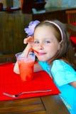 咖啡馆饮用的女孩冰冷的汁液少许 免版税库存图片