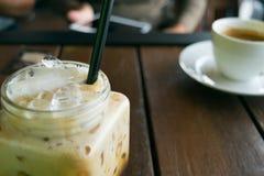 咖啡,在桌木头的被冰的咖啡在迷离妇女前面的咖啡馆 免版税库存图片