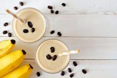 咖啡,在玻璃的香蕉圆滑的人,在白色木头的顶视图 库存照片
