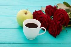 咖啡,在蓝色木桌上的苹果 顶视图 嘲笑 热的饮料 选择聚焦 红色唤醒花束 华伦泰母亲节 免版税图库摄影