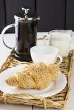 咖啡,新月形面包,在一个wattled盘子的牛奶 图库摄影