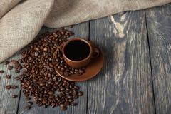 咖啡,木表面上的疏散五谷,在粗麻布旁边 免版税图库摄影
