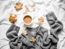 咖啡,灰色温暖特大被编织的毛线衣,在床-舒适家庭静物画,顶视图上的黄色干燥叶子 库存图片