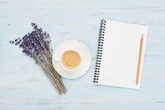 咖啡,空的笔记本和淡紫色在蓝色台式视图开花 妇女运转的书桌 舒适早餐舱内甲板位置样式 免版税库存照片