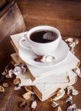 咖啡,站立在堆旧书 木背景 库存图片