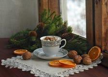 咖啡,蛋白软糖,核桃,圣诞树在一个木多雪的窗口附近分支 看板卡圣诞节新年度 免版税库存照片