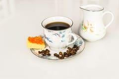 咖啡,黑或者用在一杯的牛奶,在一个茶碟,在一张白色桌上,在茶碟谎言乳酪用鱼子酱 库存照片