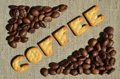 咖啡 从可食的信件的词在灰色帆布说谎 库存照片