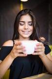 咖啡 美丽的女孩饮用的茶或咖啡在咖啡馆 有杯的秀丽式样妇女热的饮料 免版税库存图片