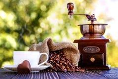 咖啡grinde和咖啡豆在书桌上 免版税库存图片
