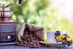 咖啡grinde和咖啡豆在书桌上 免版税库存照片
