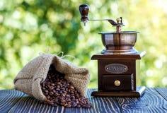 咖啡grinde和咖啡豆在木书桌上 免版税库存图片