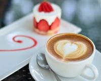 咖啡latte艺术和草莓蛋糕 库存照片