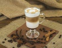 咖啡Latte 与被鞭打的奶油色顶部的咖啡在一块高玻璃 库存照片