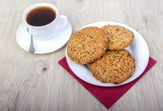 咖啡wiyh堆各种各样的脆饼和燕麦曲奇饼用在木背景的谷物 免版税库存图片