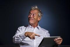 咧嘴和指向他的片剂的老人 免版税图库摄影
