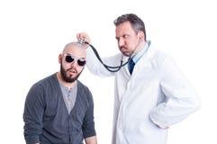 咨询一名疯狂的患者的男性医生与听诊器 免版税图库摄影