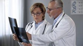 咨询关于联接X-射线,治疗的结果的男性和女性医师 库存照片
