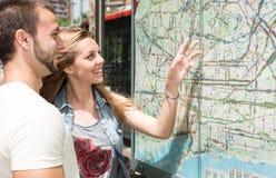 咨询地图的年轻夫妇 免版税库存图片