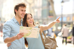 咨询城市的游人夫妇引导搜寻地点 免版税库存照片