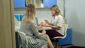 咨询女性患者的妇产科医师医生使用子宫解剖学模型 免版税库存照片