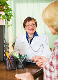 咨询女性患者的成熟医生 免版税库存照片