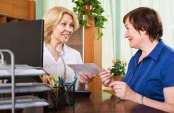 咨询女性患者的成熟医生 库存图片