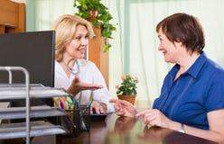 咨询女性患者的成熟医生 免版税库存图片