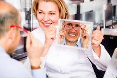 咨询成熟男性顾客的友好的女性眼镜师 免版税库存照片