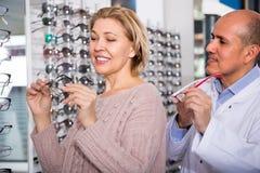 咨询成熟白肤金发的顾客的男性眼镜师在眼镜显示附近 免版税库存照片