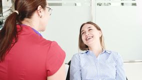 咨询的一少女与玻璃的一名牙医妇女坐一把椅子在stamotology办公室 ?treadled 股票录像