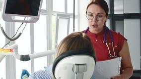 咨询的一少女与玻璃的一名牙医妇女坐一把椅子在stamotology办公室 ?treadled 影视素材