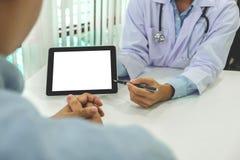 医治咨询的患者并且推荐治疗方法,并且如何使身体恢复原状,提出在片剂计算机上收效 免版税库存照片