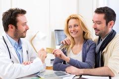 付咨询的年轻有吸引力的夫妇到医生 免版税库存照片