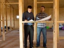 咨询计划的建造者在一个半建造的房子里 库存图片