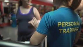 咨询超重夫人的健身教练员行使在健身房, weightloss控制 股票录像