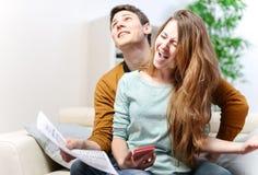 咨询他们的银行帐户的愉快的年轻夫妇充满喜悦 库存照片