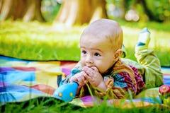 咬住一个木玩具的逗人喜爱的男婴 免版税库存照片