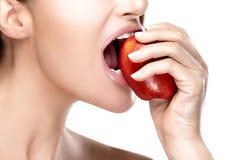 咬住大红色苹果计算机的美丽的健康嘴 库存照片