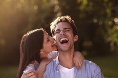 咬住她的男朋友的耳朵的少妇 免版税库存照片